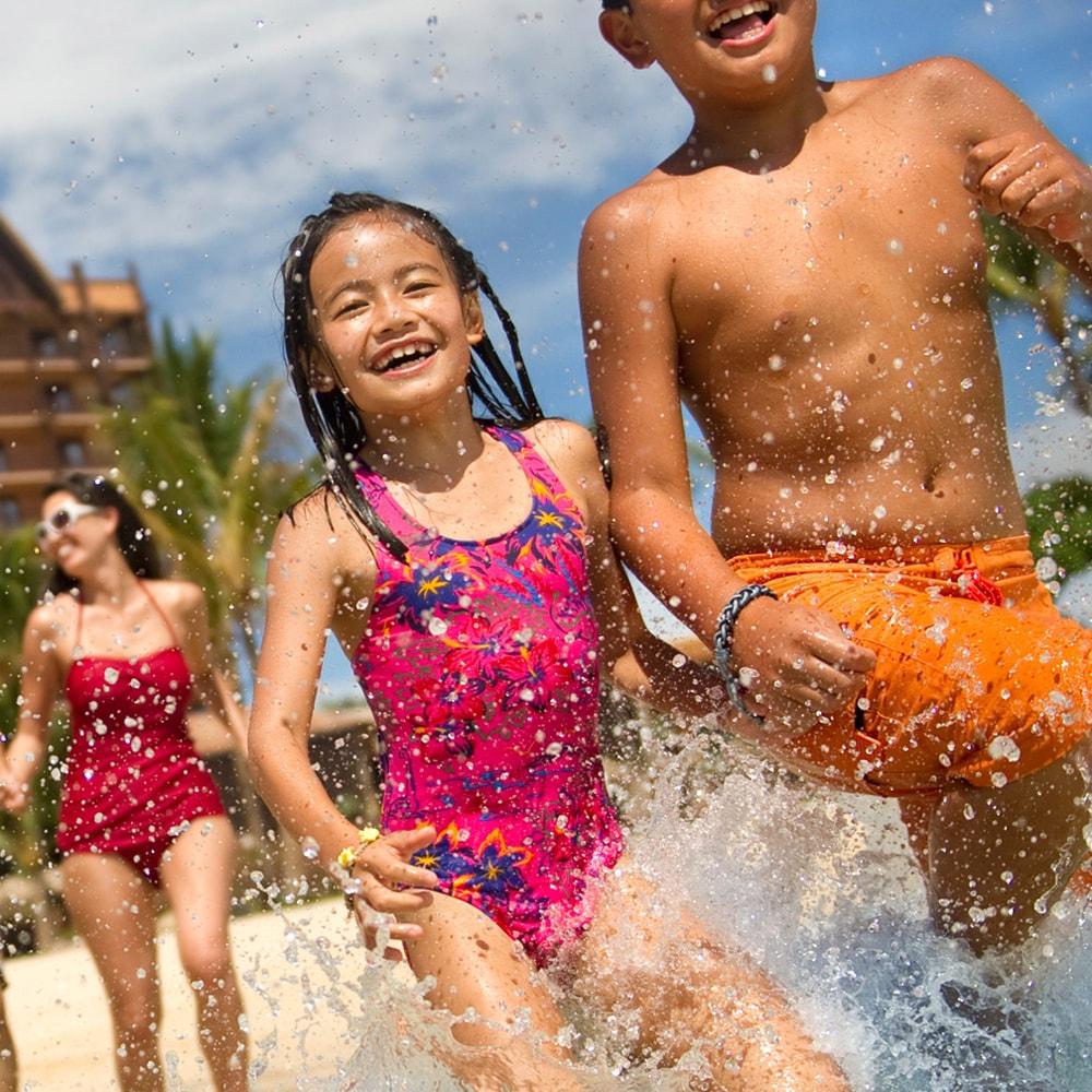 コオリナ・ビーチで水しぶきをあげて遊ぶファミリー