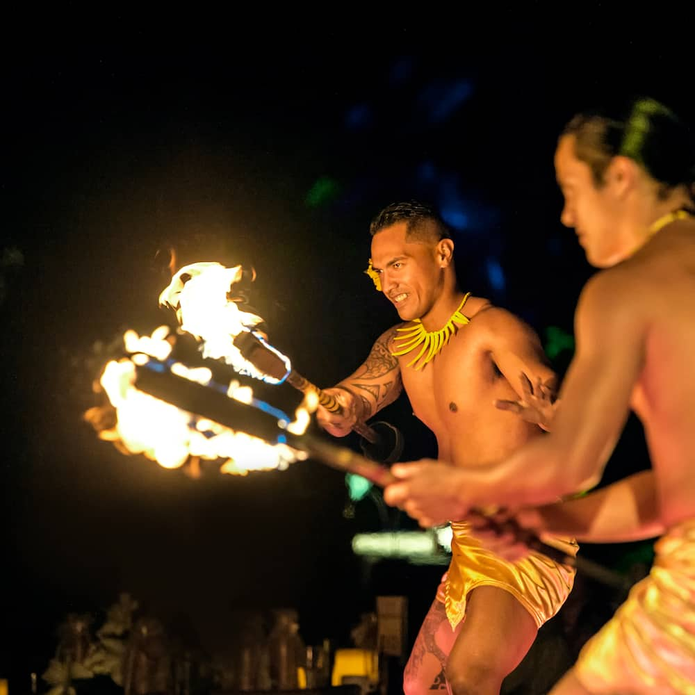 Two male fire performers wave flaming torches in a traditional Hawaiian dance