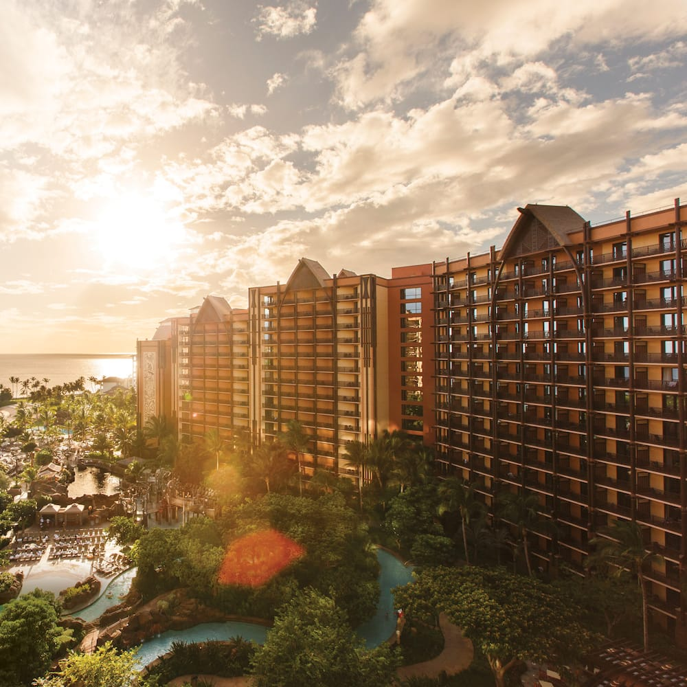 Three towers of Aulani resort with a sunset in the background