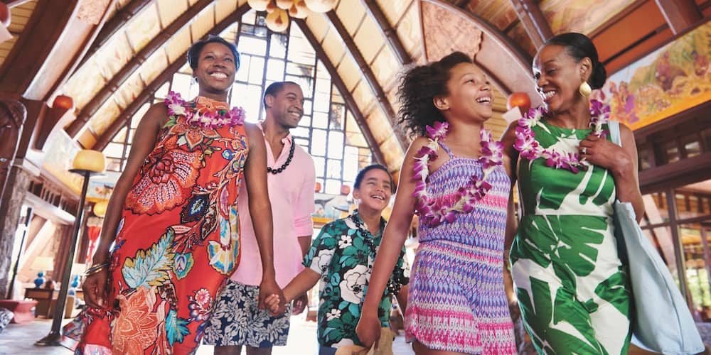 A multi-generational family smile and laugh as they walk through the main lobby at Aulani Resort wearing flower and kukui nut leis