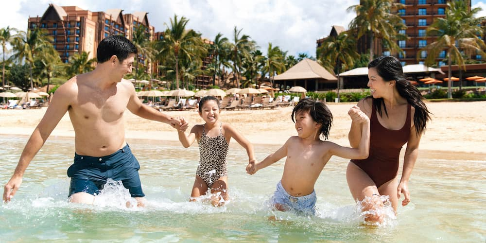 A father, mother, son and daughter holding hands as they wade in the lagoon at Aulani, A Disney Resort & Spa