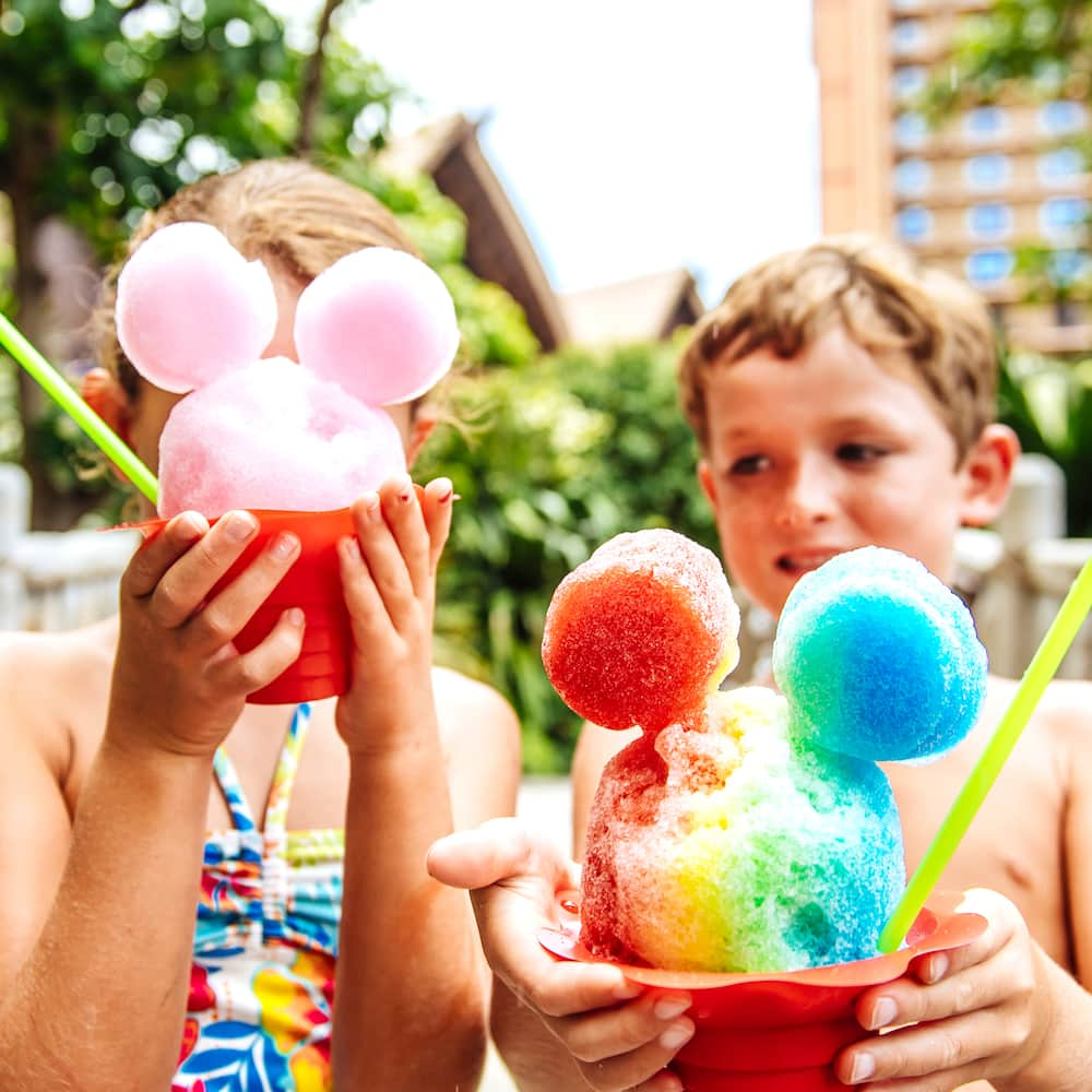 Two children hold their Papalua Shave Ice, shaped to resemble Mickey Mouse's head