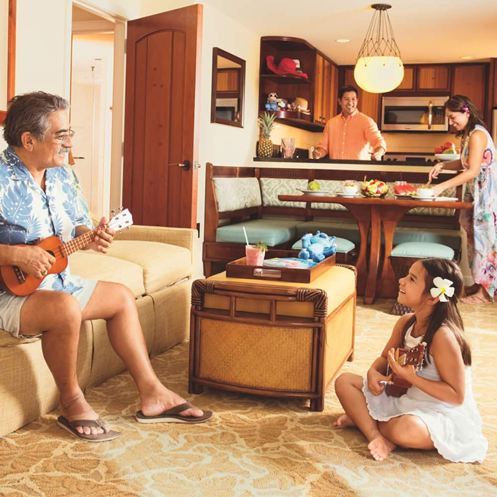 A man sits on a couch playing a ukulele while a couple prepares food in the dining area