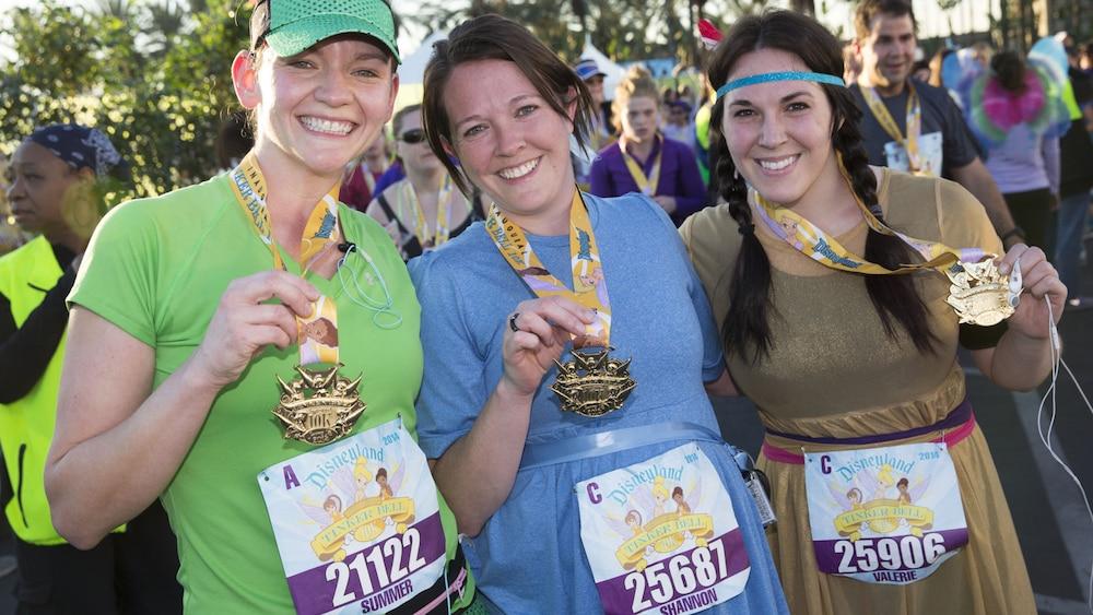 「Disneyland Tinker Bell 10k」と書かれたゼッケンをつけたピーターパンのコスチュームを着てメダルを見せる 3 人の女性