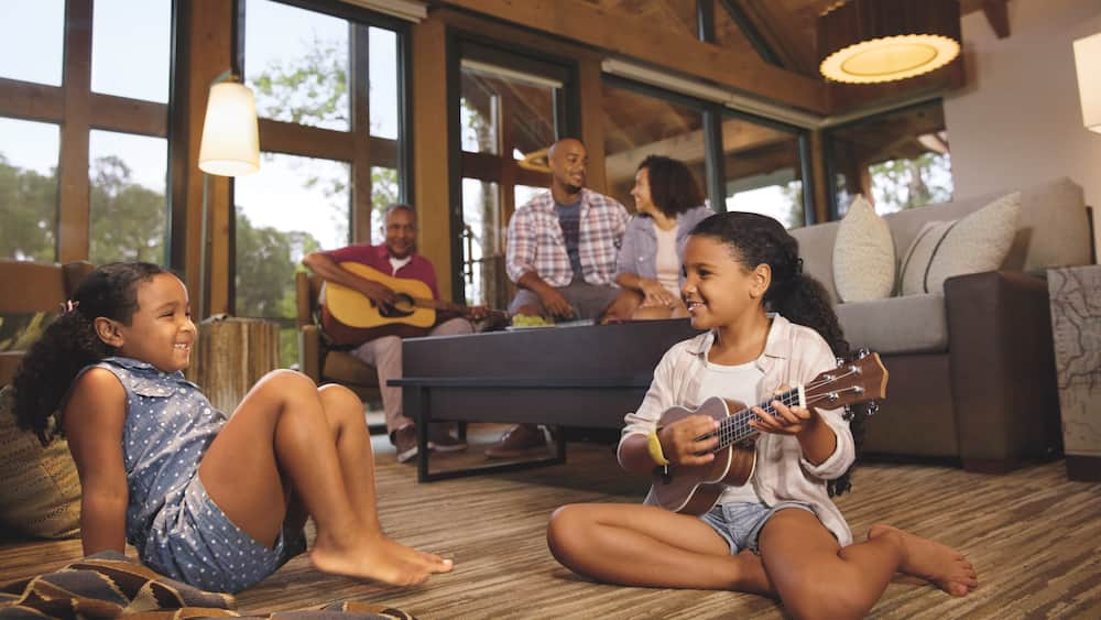 A young girl plays a small guitar while sitting on the floor of her cabin, as her parents relax on the couch behind her