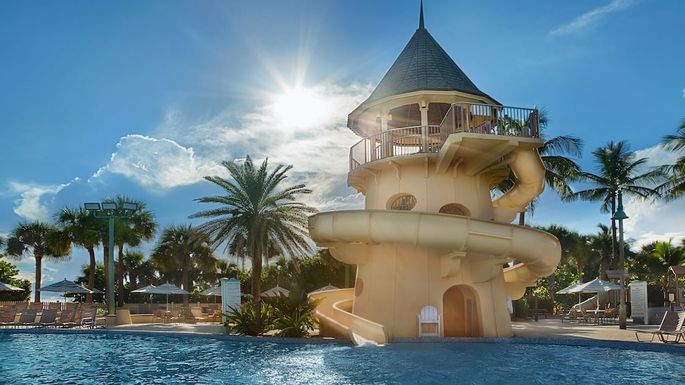 An outdoor swimming pool with a castle themed waterslide at Disney's Vero Beach Resort