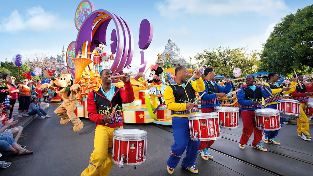 A parade at Disneyland Park featuring a drumline, parade floats and Disney Characters