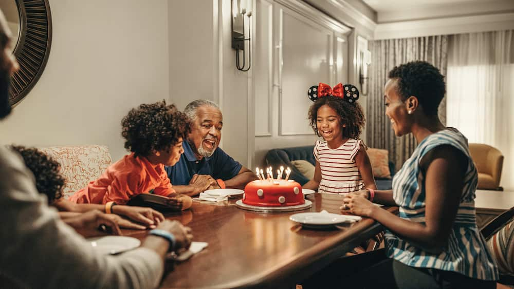 A family of 6 sits at a kitchen table at Disney's Riviera Resort, ready to enjoy birthday cake