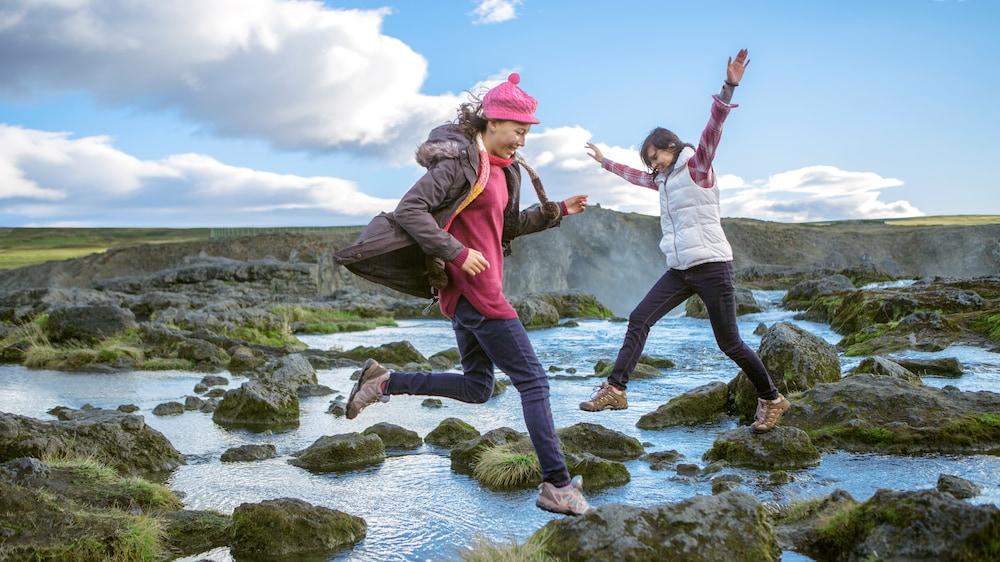 2 teenage girls jumping beside a river