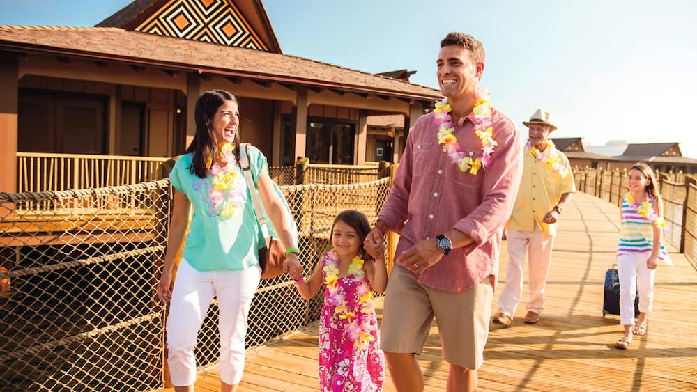 A grandfather, father, mother and 2 children walking on an outdoor pier