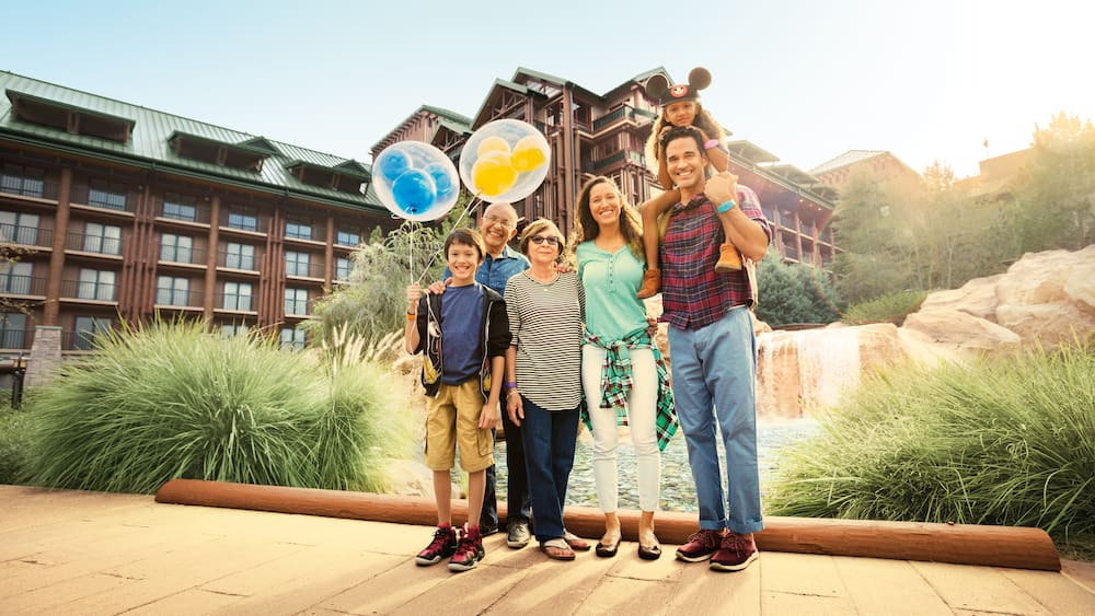 A family holding balloons stands in front of a waterfall at Disney's Wilderness Lodge
