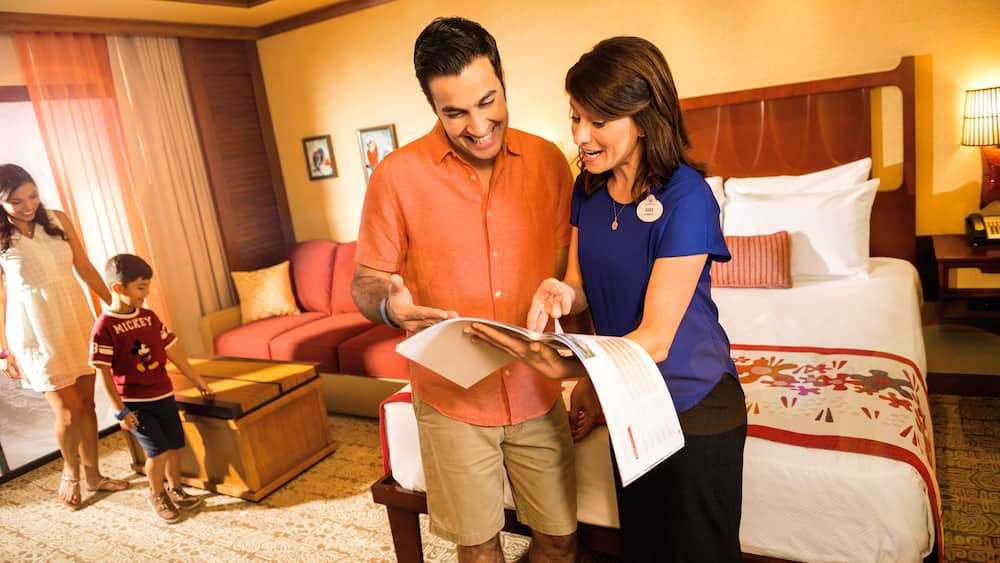 A Cast Member giving a Disney Vacation Club villa tour to a man, woman and their young son