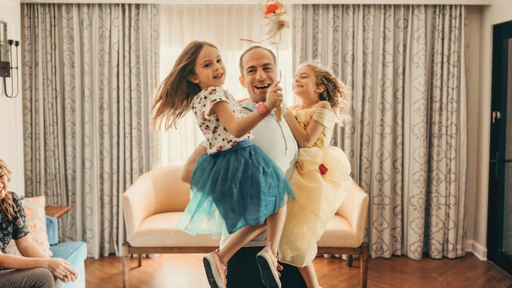 A father dances with his 2 daughters in the living area of a villa at Disney's Riviera Resort