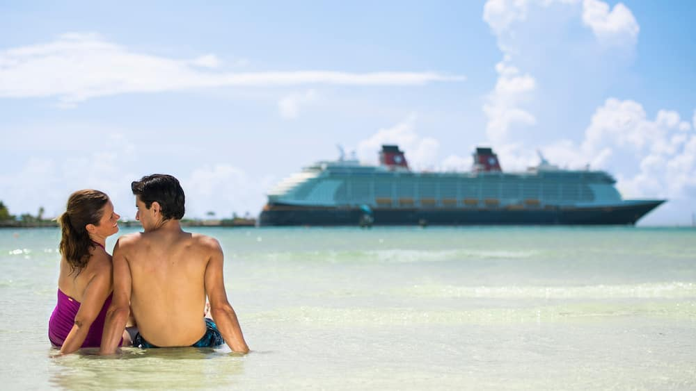 A man and woman lounging in shallow water near a Disney Cruise Line ship