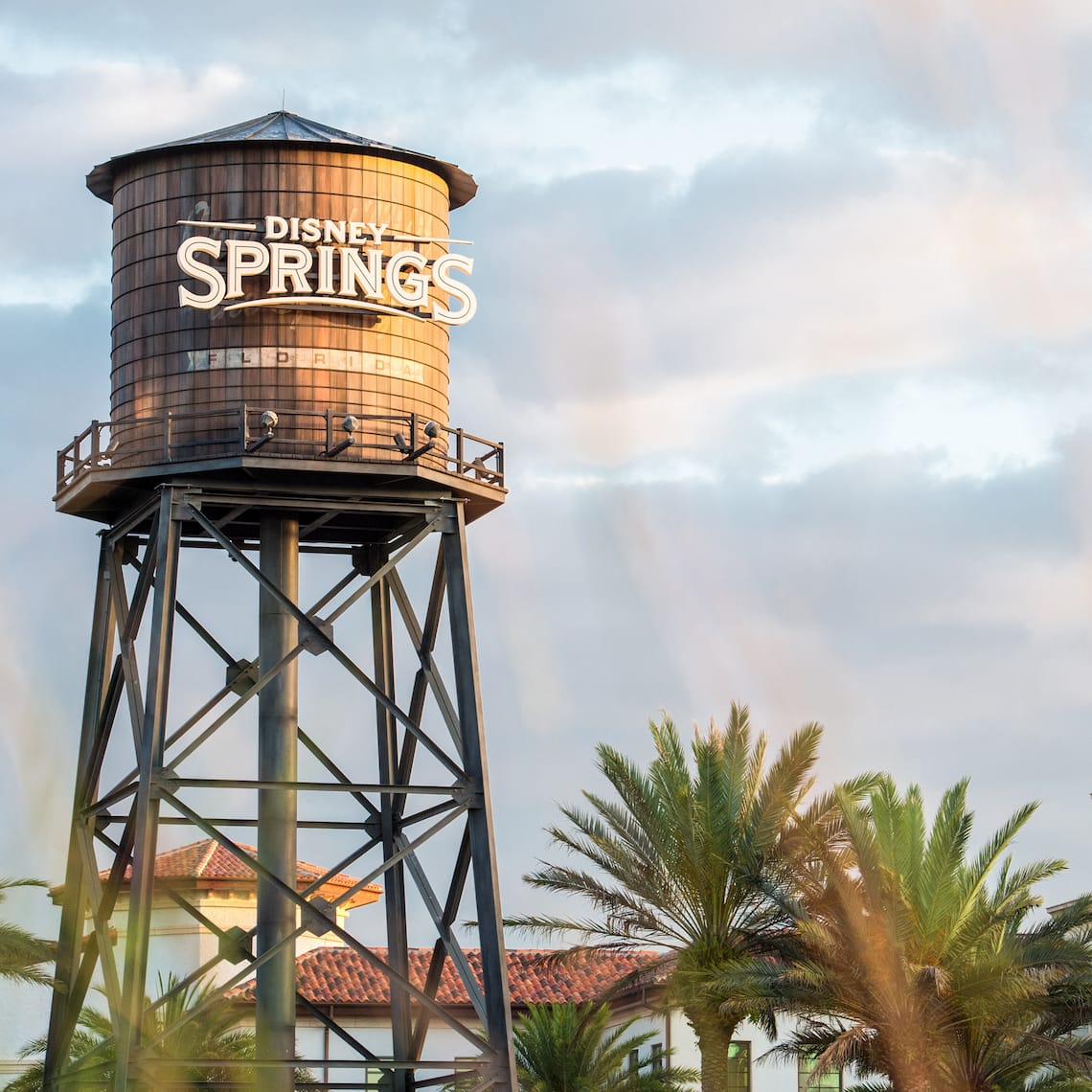 A water tower that reads Disney Springs is surrounded by buildings and palm trees