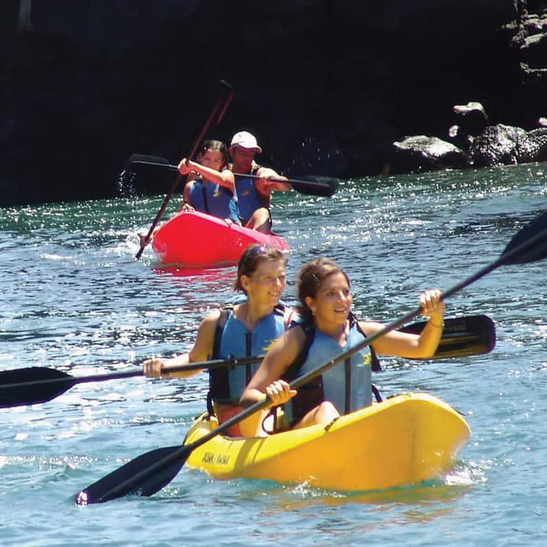 Kids paddle 3 kayaks in the water near a tropical, cliff-hung coastline