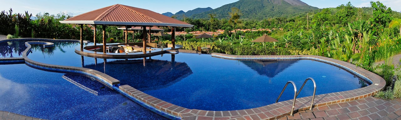 The pool at the Hotel Arenal Manoa with a swim-up bar in the middle and view of Arenal Volcano in the distance