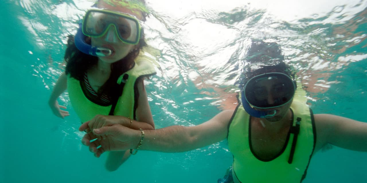 A couple hold hands while snorkeling underwater wearing snorkeling masks and vests