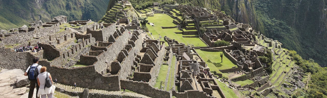 A couple stands on a stone terrace above Machu Picchu