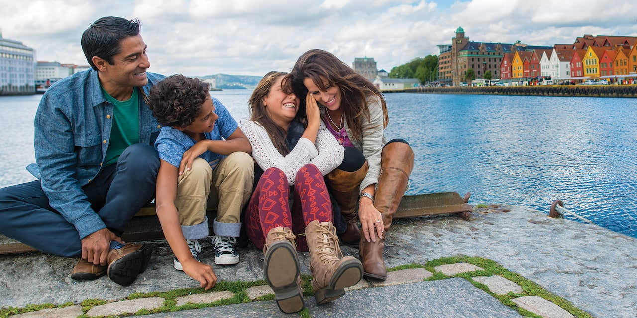 A family of 4 with older children sit on a dock across a fjord from a quaint town