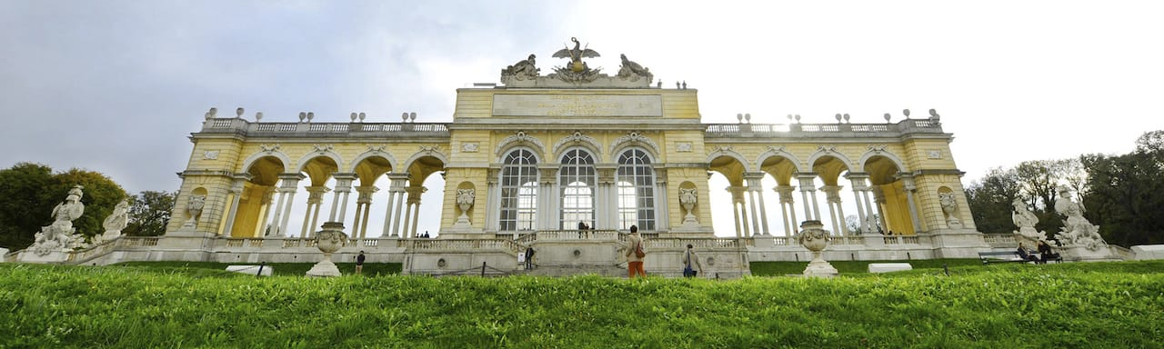 Looking up at Schönbrunn Palace from the bottom of a grassy hill