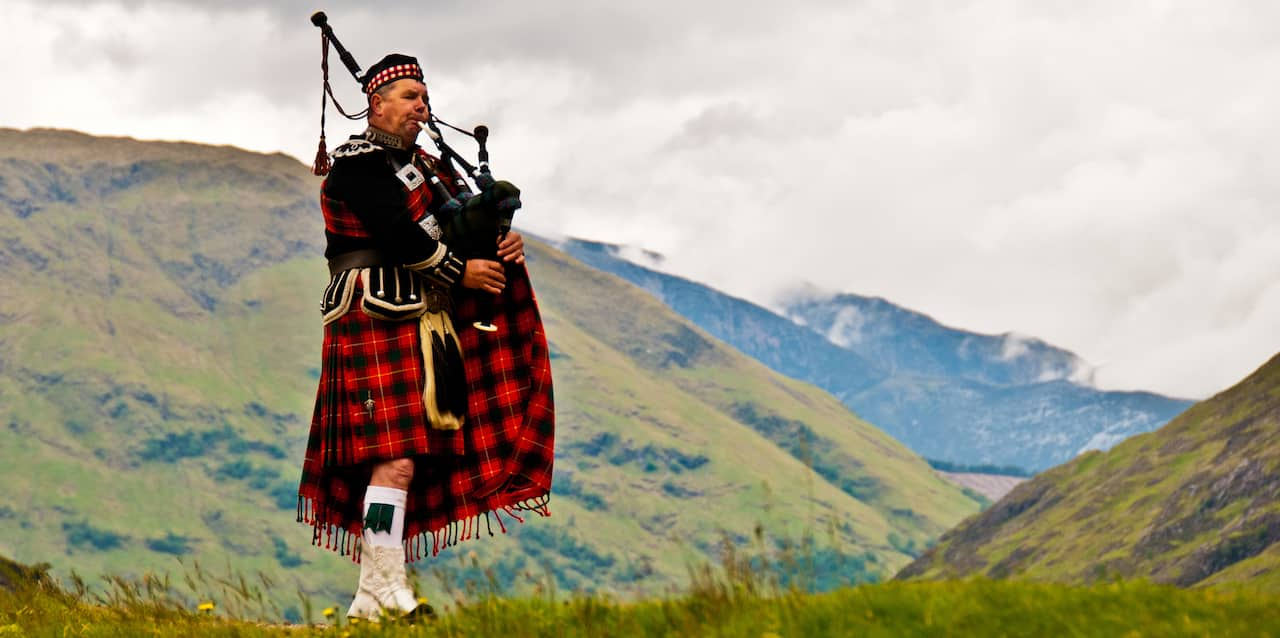 A Scotsman wearing a tartan kilt and traditional Scottish clothing stands in the hills playing a bagpipe