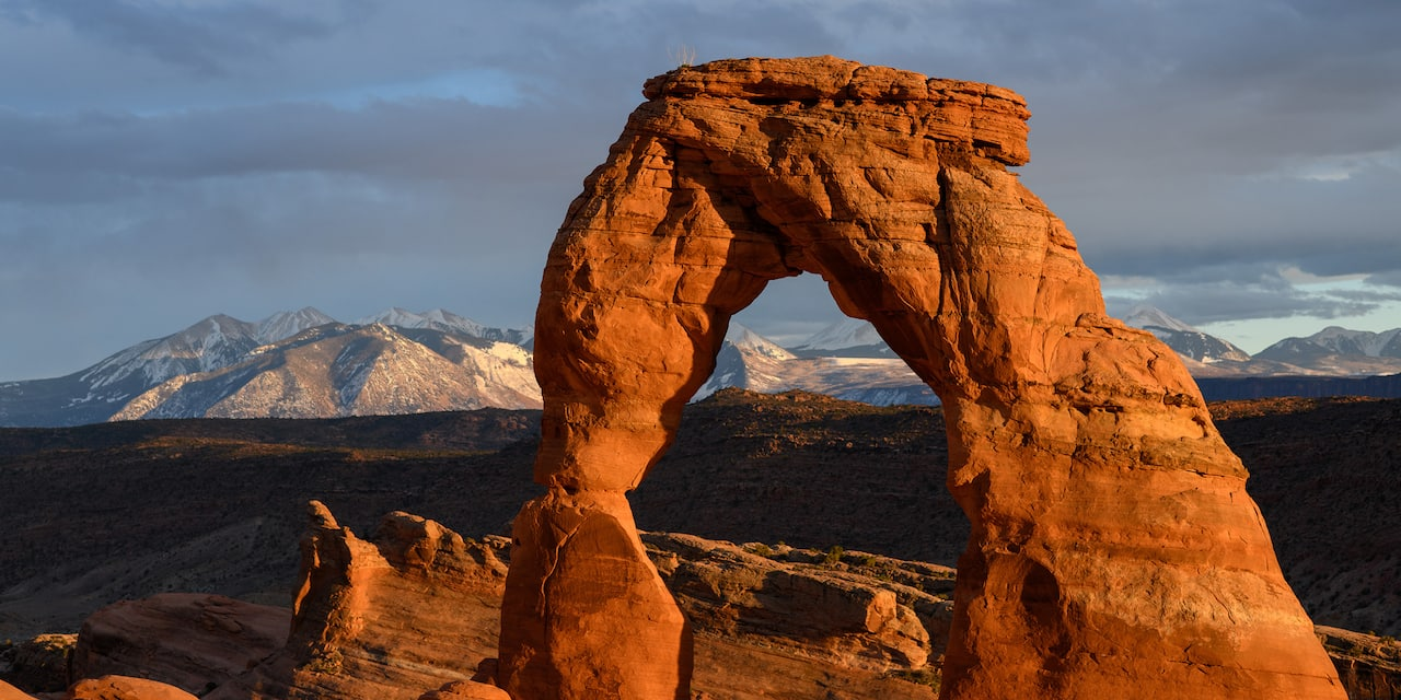A natural sandstone arch in Arches National Park with snow-capped mountains in the background