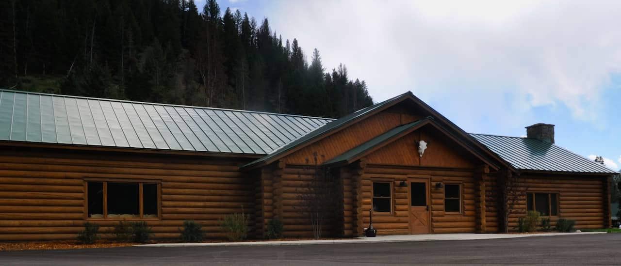 A lodge surrounded by pine-covered mountains