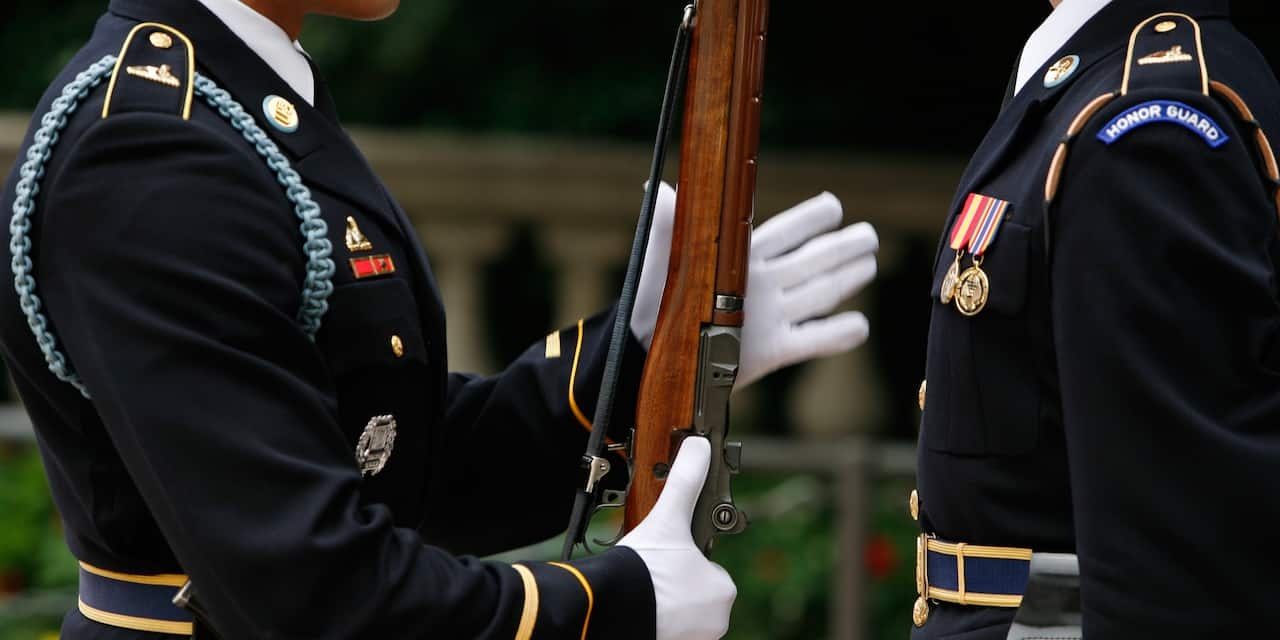 Two Honor Guards at the Arlington National Cemetery, with one holding a rifle as he presents arms
