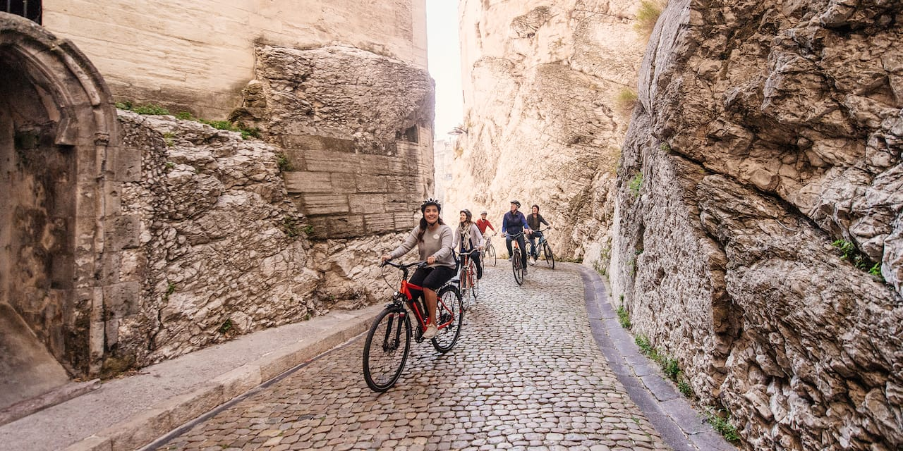 A group of people ride bicycles on a cobblestone street that is lined with large stone buildings