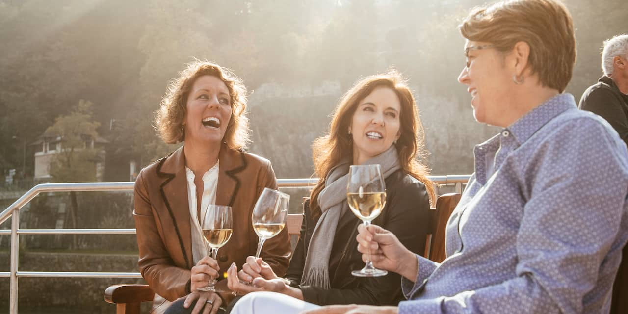 Three women with glasses of wine enjoy a discussion while seated on an outside deck of a river boat as they pass a tree-lined shore