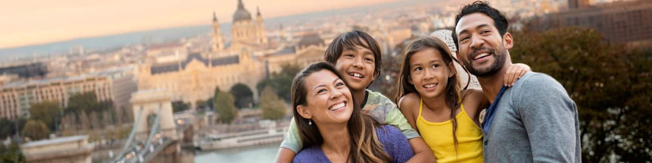 A family of Guests pose for a picture with a wide view of the city's historic buildings behind them