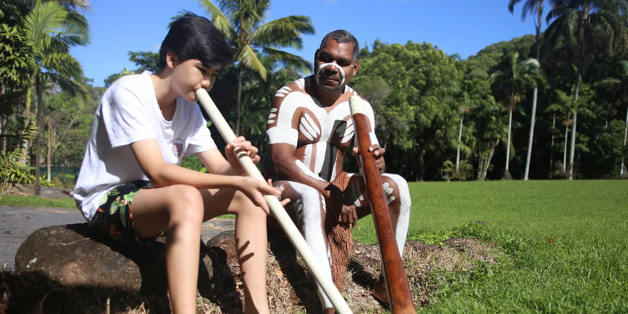 A boy blowing a didjeridu with a man of Aboriginal descent looking on