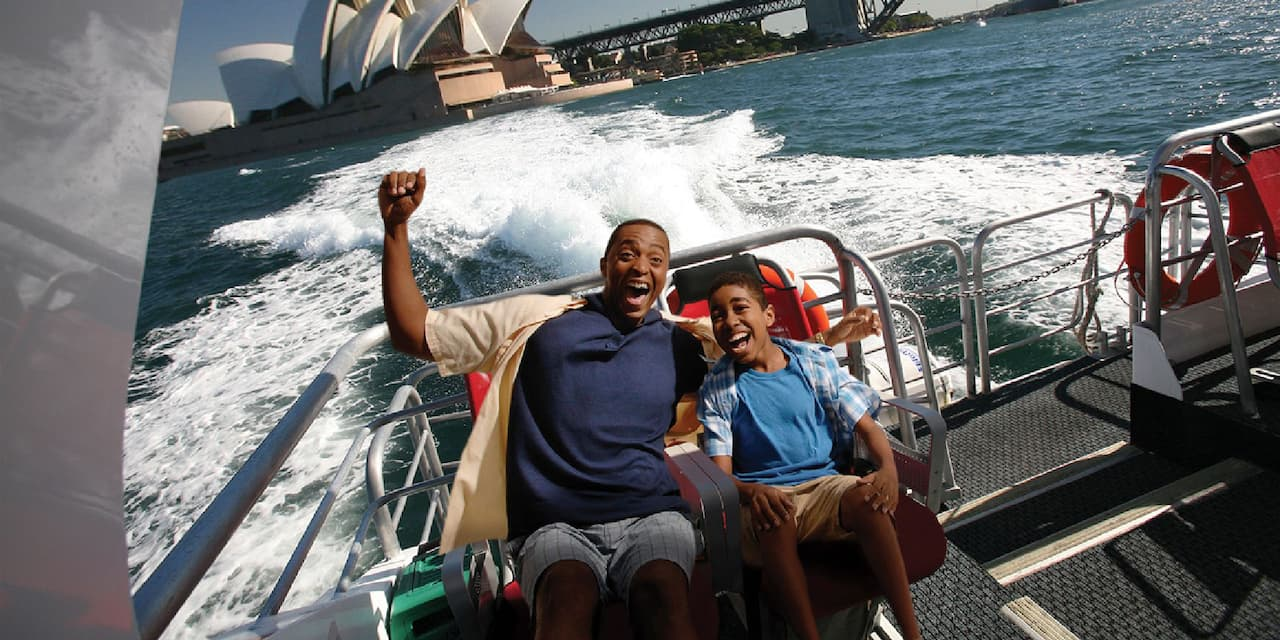 A man and a boy ride a speed boat through Sydney Harbour