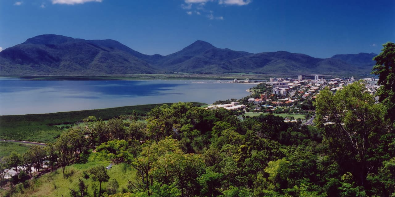 The city of Cairns, tucked between a mountain range, a lake and lush forest
