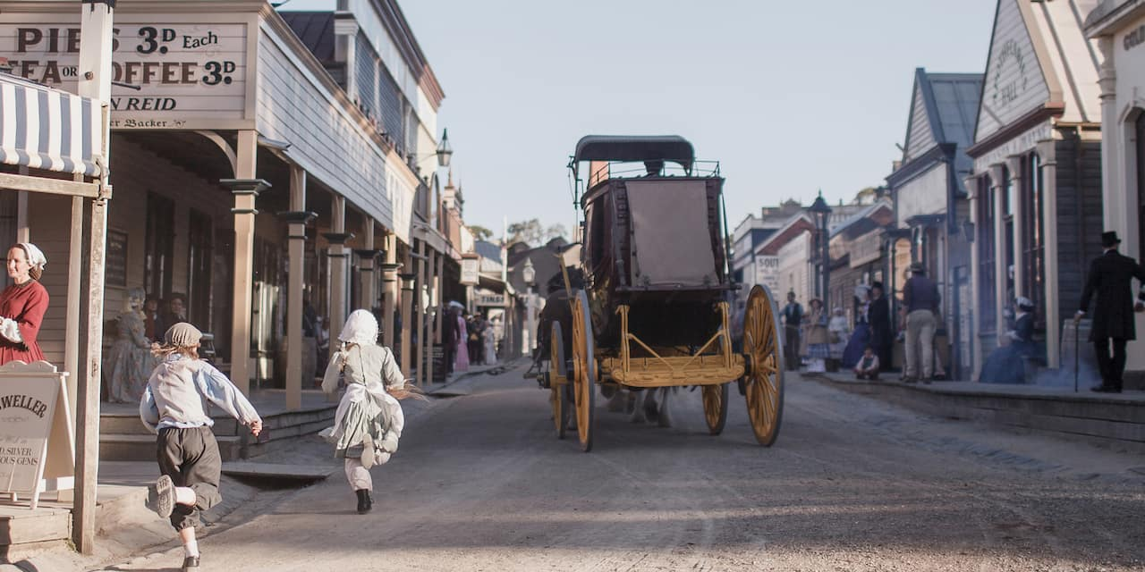 Two kids run after a horse drawn buggy travelling down a dirt road lined with shops and people all dressed in 1800s era clothing at the Sovereign Hill open air museum in Melbourne, Australia