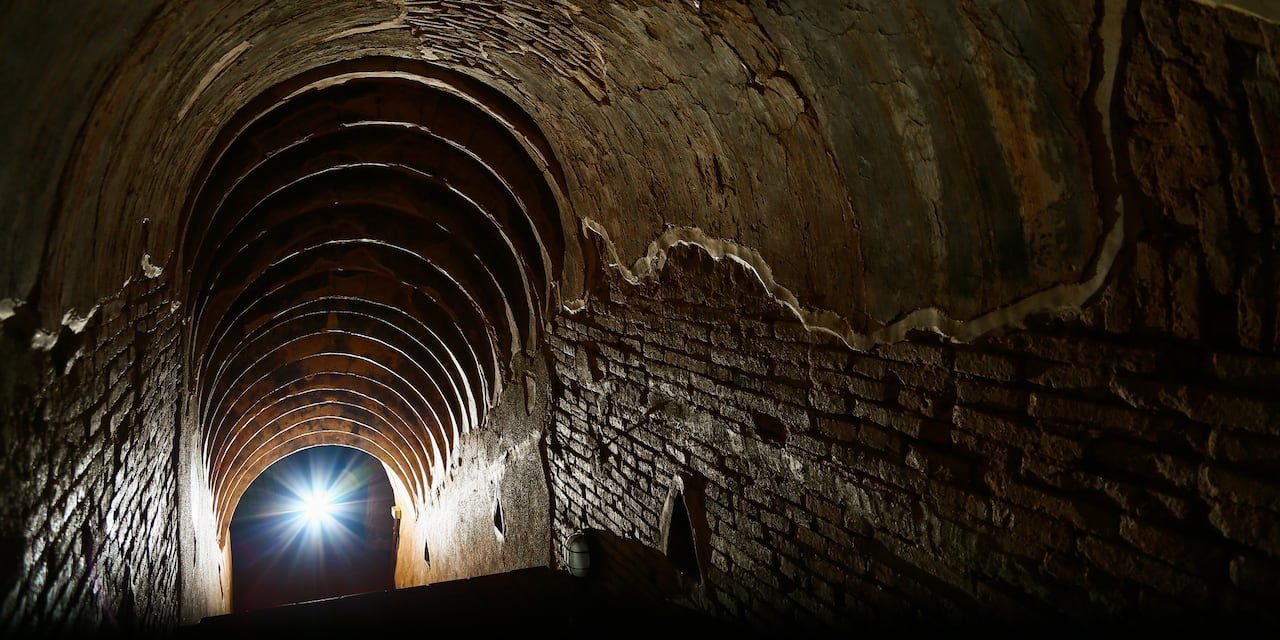 A dark, brick-walled tunnel with an arched ceiling leads downward towards a bright light at the Cú Chi Tunnels