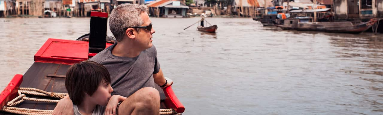 A father and son drift past a Mekong River village while sitting in a canoe
