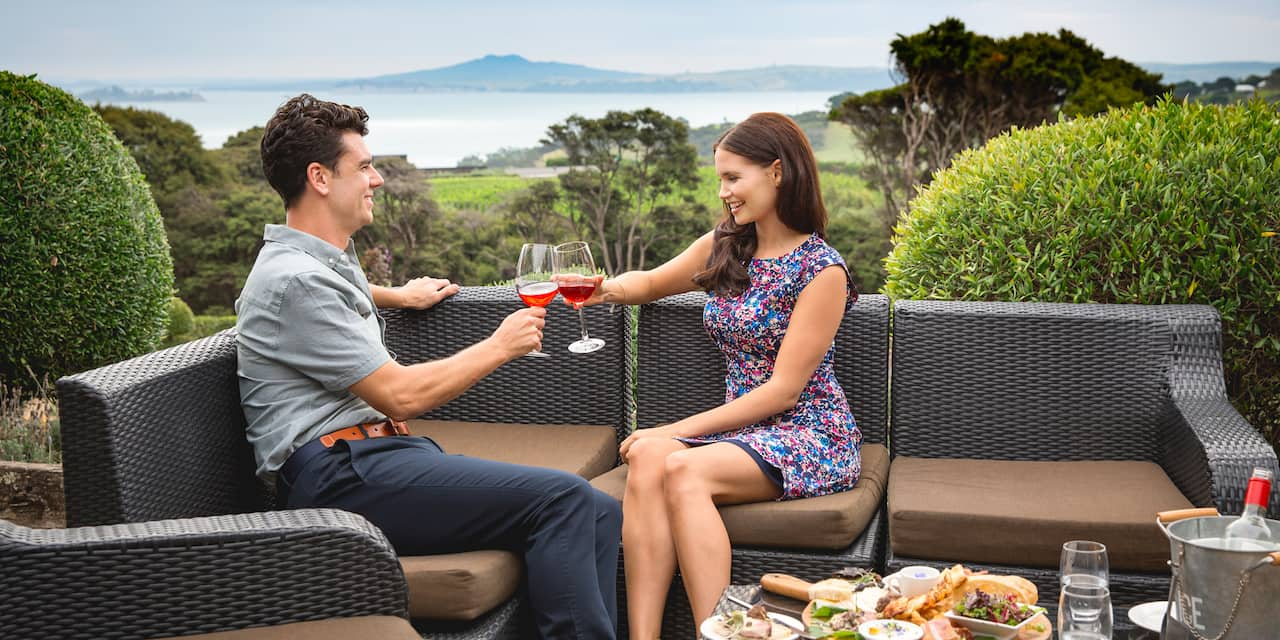A smiling couple in wicker chairs toasts with large wine glasses while seated in front of a backdrop view of the sea and a distant mountain