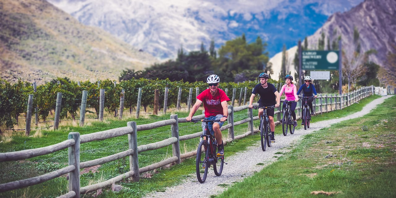Four people ride bicycles on a path along a wooden fence in the mountains