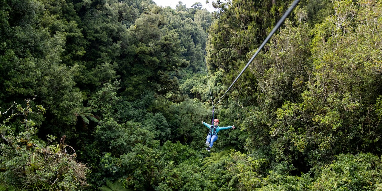A person zip lines through tree tops with their arms outstretched