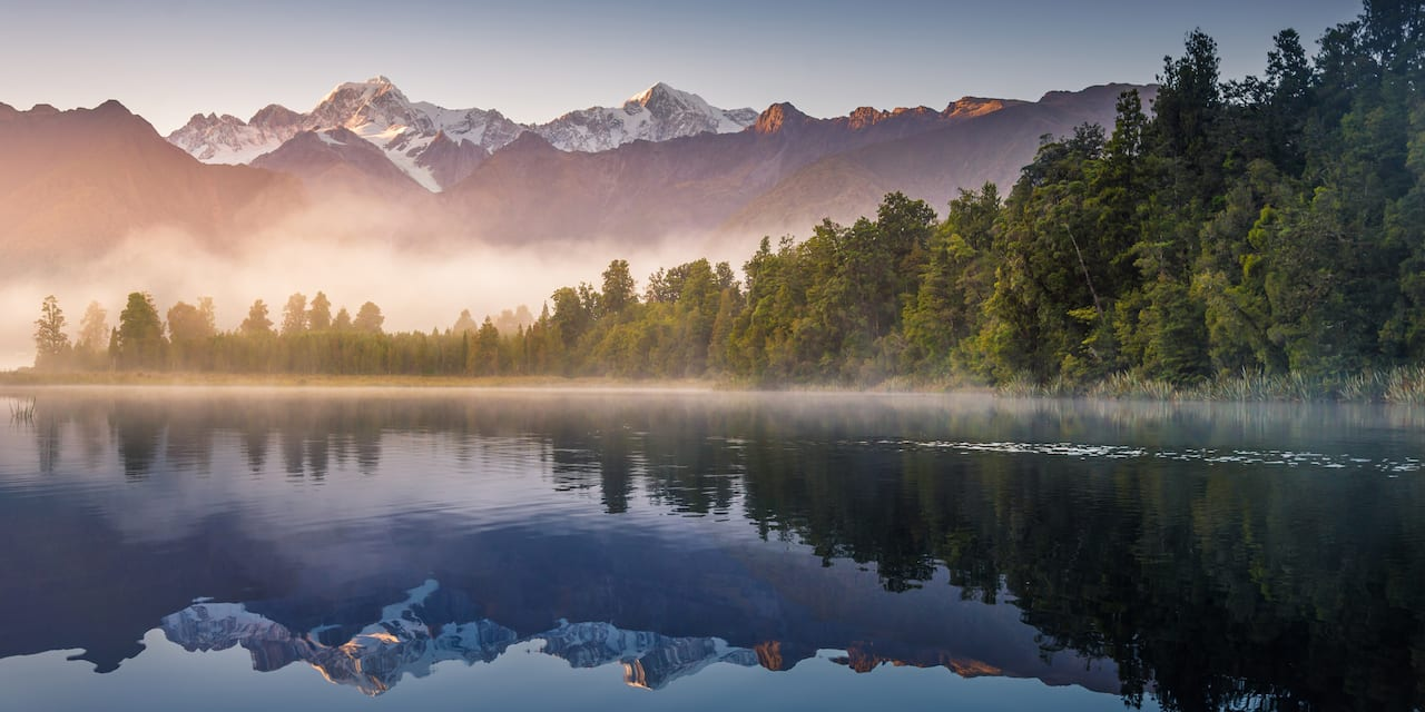 Mist rises from Wanaka Lake with tree covered banks near a mountain range at dawn