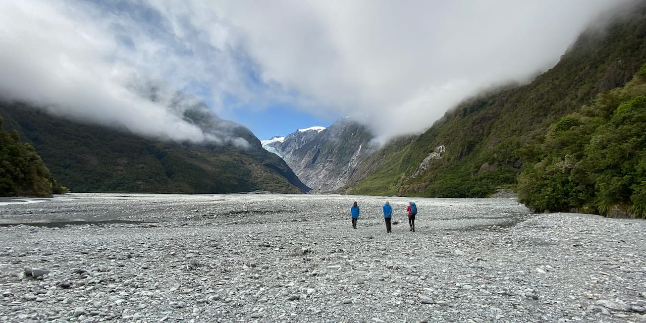 Three people walk on a stone wash towards a glacier between mountains enshrouded by clouds