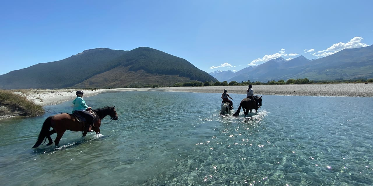 Three people ride horses through a river to a sandy bank