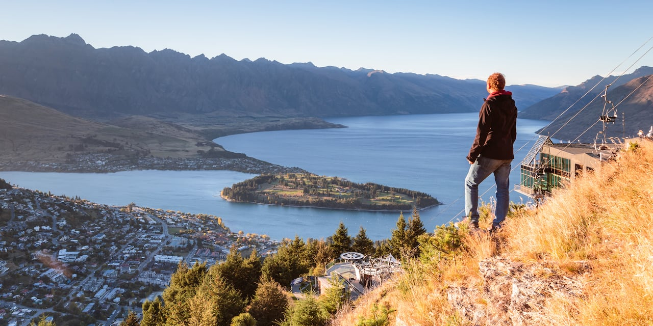 A man stands on a hill looking down on the city of Queenstown and Lake Wakatipu