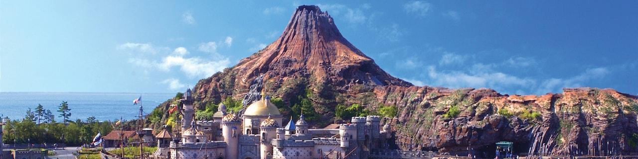 The giant volcano, Mt. Prometheus, looms over a domed building on Arabian Coast Island at Tokyo DisneySea