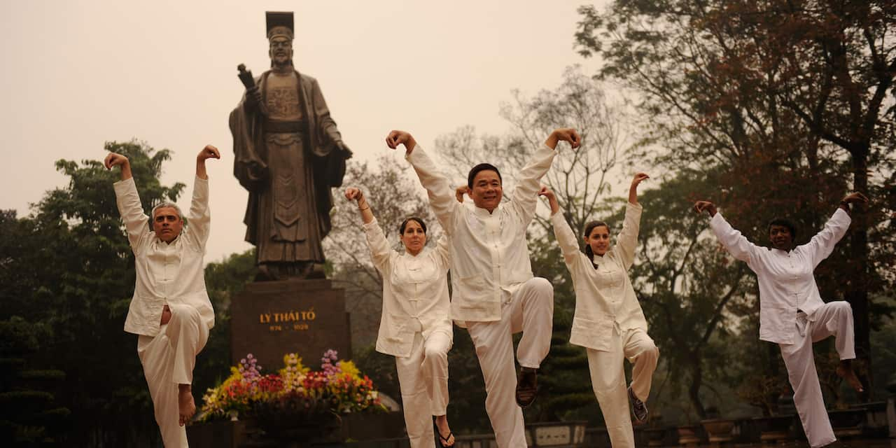 People raise their arms and one of their legs in an outdoor Tai Chi class