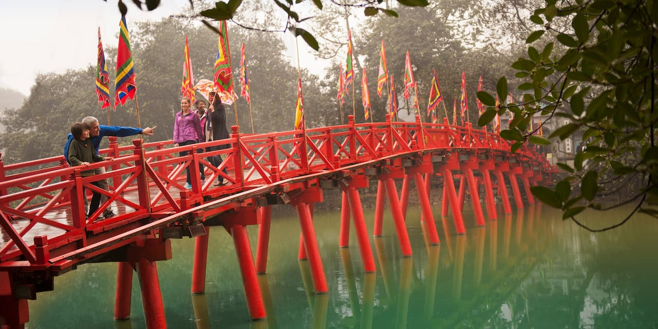 A group of people, including a man pointing something out to a boy, cross over a lake on a bridge that is decorated with flags