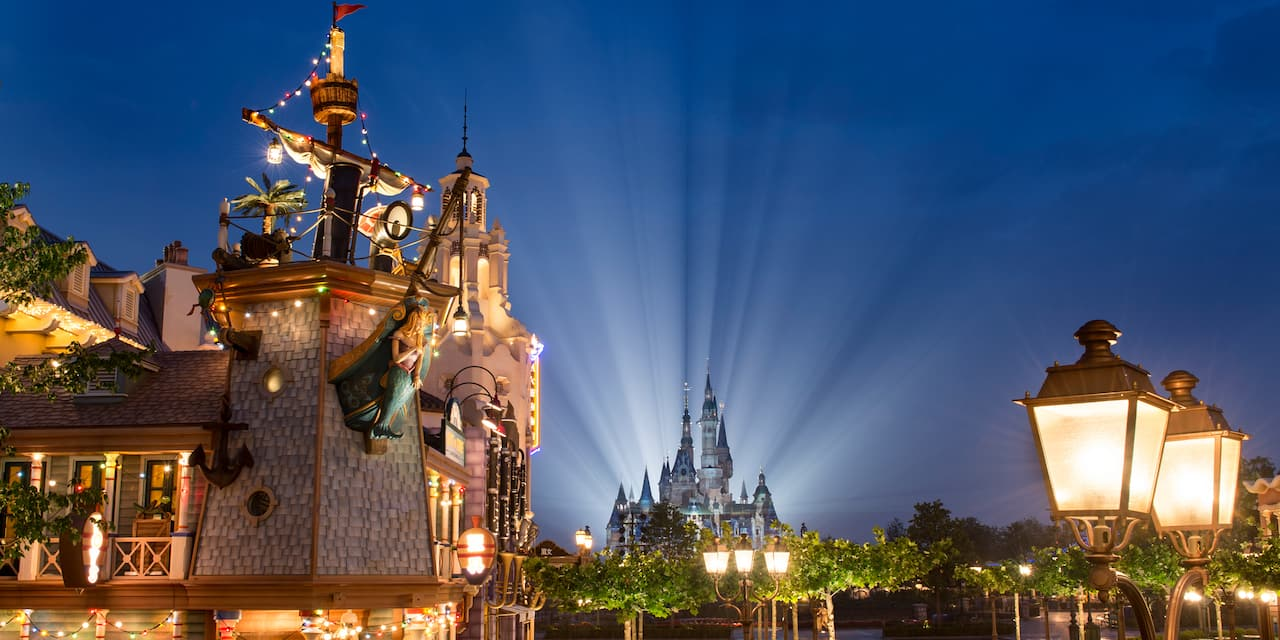 Treasure Cove and Enchanted Storybook Castle are lit up at night at Shanghai Disneyland
