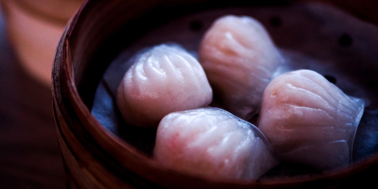 Four dumplings in a bamboo steamer